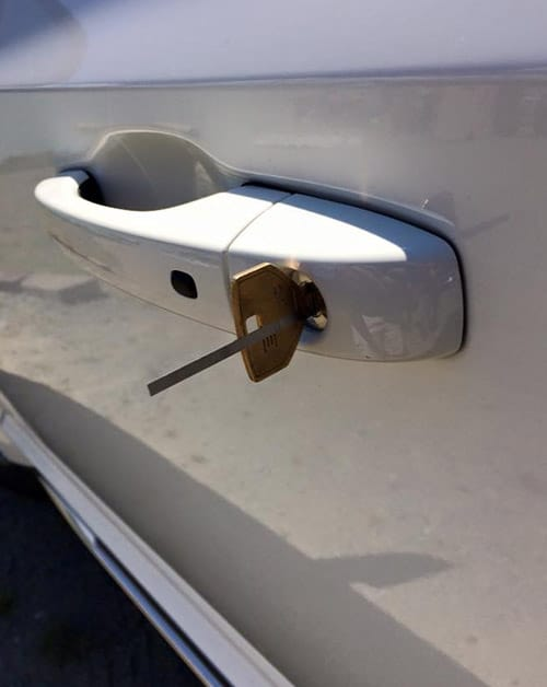 image of a car door lock with lock picking tools