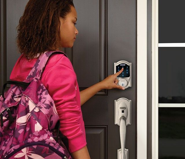 image of a young woman typing her pass code into a residential smart lock keypad